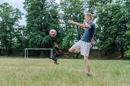 The man with a dog is playing with a soccer ball.