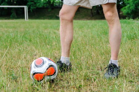 Mens legs are on the grass. There is a soccer ball next to it.