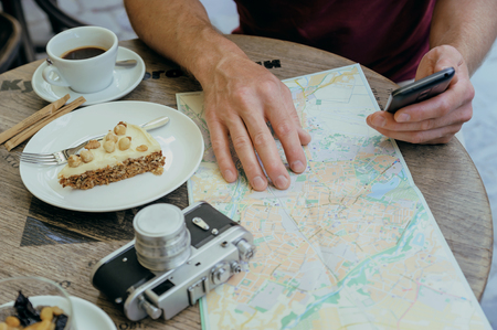 A man is holding a smartphone. He is sitting at the cafe table on the street. On the table there is a vintage camera, a tourist map, a coffee and a piece of cake on a plate.