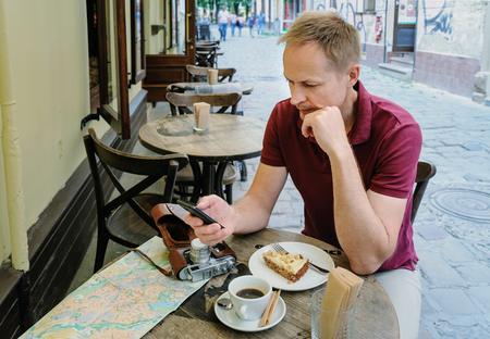 The man is holding a smartphone. He is sitting at the cafe table on the street. On the table there is a vintage camera, a tourist map, a coffee and a piece of cake on a plate.