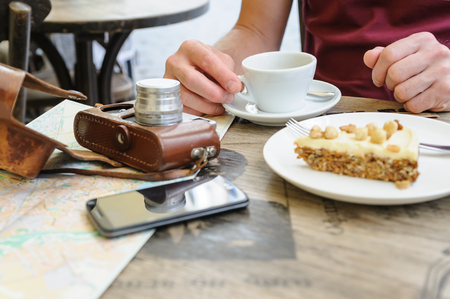 A man is sitting at the cafe table on the street. On the table, there is a vintage camera, a tourist map, a coffee and a piece of cake on a plate.
