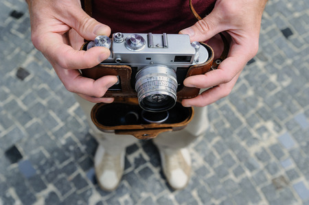 A man is holding a vintage camera. With one hand it is changing the setting. Top view.