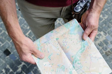 A man is holding a tourist map. Top view. Фото со стока