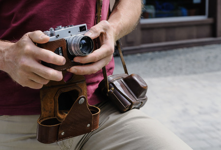 A man is holding a vintage camera. One of his hand is setting the lens. Фото со стока