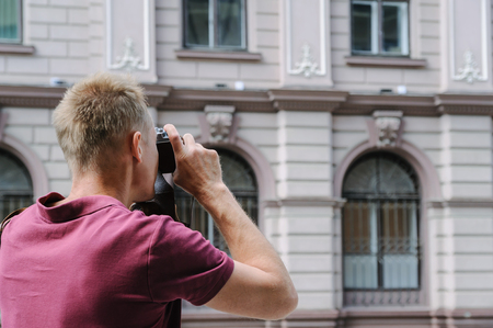 A man is photographing an old house. He is using a vintage camera.