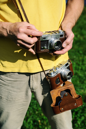 A man has two vintage photo cameras in leather cases. One camera holds a hand. Фото со стока