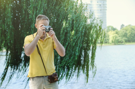 The man is photographing an old camera on a tree and lake background.