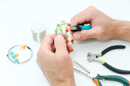 A man is using pliers to create an ornament from a silver wire. Handmade jewelry.