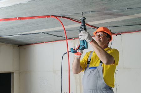 An electrician is drilling a ceiling with a perforator in order to fix the corrugated pipe.