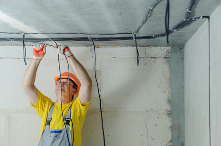 An electrician is fixing an electric cables to the ceiling. Фото со стока