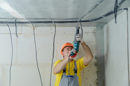 An electrician is drilling a ceiling with a perforator in order to fix electrical cables. Фото со стока