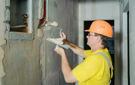 The worker is holding trowels with a gypsum. It is covering the electric corrugated tubes in the wall. Фото со стока