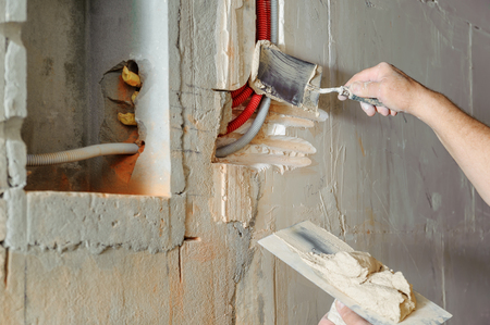A worker is holding trowels with a gypsum. It is covering the electric corrugated tubes in the wall. Фото со стока