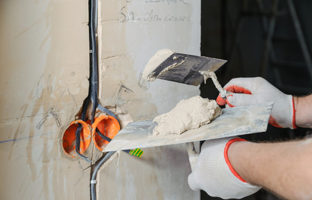 A worker is holding trowels with a gypsum. It is covering the electric cables in the wall.