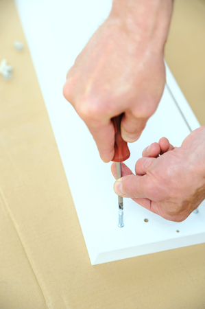 A man is installing Joint Connector Bolts in the furniture board.