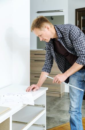 Mounting the chest of drawers. The man is looking for an instruction for furniture assembly. Stock Photo