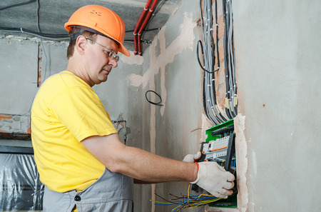 The electrician installing the fuses in the switch box. Stock Photo