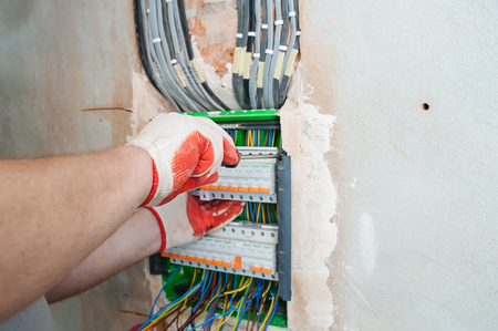 A electrician installing the fuses in the switch box. Фото со стока