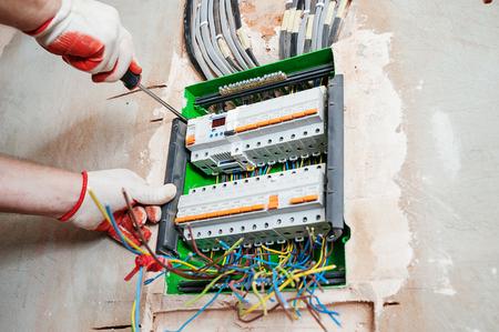 Un electricista instalando los fusibles en la caja de interruptores. Foto de archivo