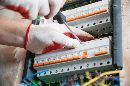 A electrician is installing the fuses in the switch box. Stock Photo