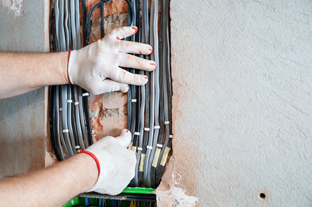 An electrician is installing electric wires in a switching fuse box. Фото со стока