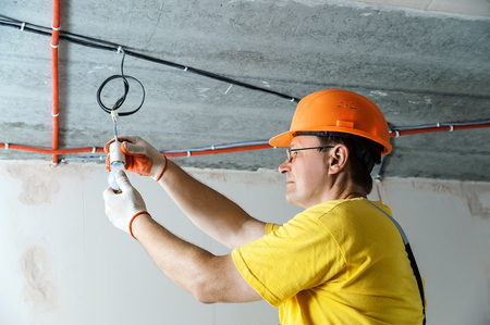 The electrician is setting a light bulb for temporary lighting. Stock Photo