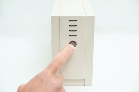 The index finger is pressing on the start button of the uninterrupted power supply. Фото со стока