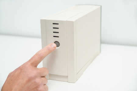 The index finger is pressing on the start button of the uninterrupted power supply. Stock Photo