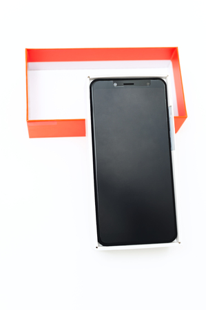 The black smartphone is in the white box. Near is the orange top. Stock Photo