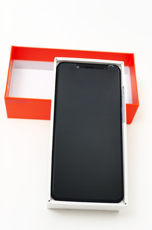 The black smartphone is in the white box. Near is the orange top. Фото со стока