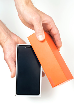 Human hands are holding a box with a smartphone.
