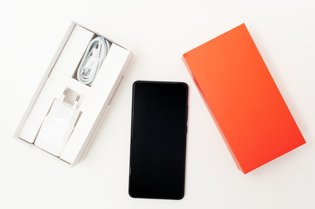 Black smartphone on a white background. Along with this there is a box with a power supply and a charging cable, as well as an orange top. Stock Photo
