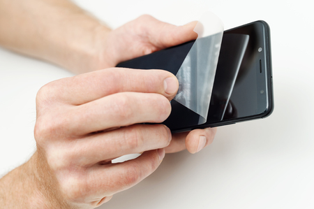 Human hands are removing a protective film from the screen of a smartphone. Фото со стока
