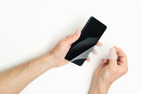 Human hands are removing a protective film from the screen of a smartphone. Stock Photo