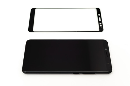 Black smartphone and a protective glass on it on a white background.