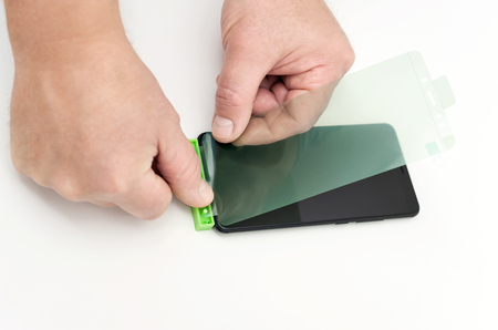The man is glueing a protective film on the smartphone screen with the fitting. Фото со стока