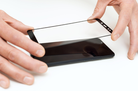 A man is glueing a protective glass on the screen of a smartphone. Фото со стока