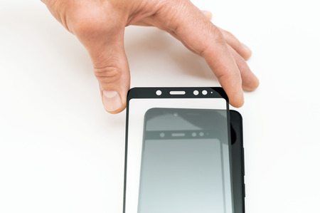 A man is glueing a protective glass on the screen of a smartphone. Stock Photo