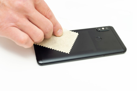 A man is wiping the body of the smartphone with a microfiber cloth.