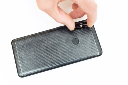 A man is installing a protective glass on the back lens of the smartphone. Stock Photo