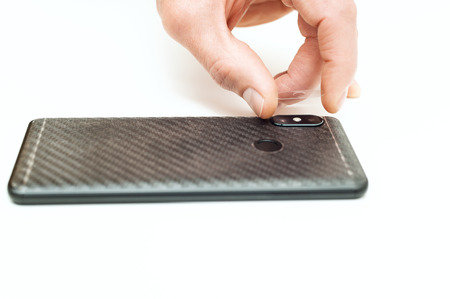 A man is installing a protective glass on the back lens of the smartphone. Фото со стока