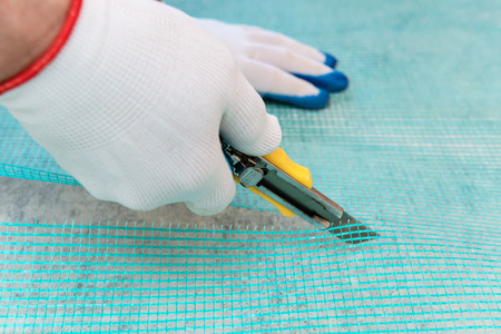 A worker is cutting off a piece of mesh with a knife. Stock Photo