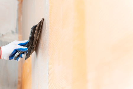 A worker is applying putty on a mesh on the wall. He is using a wide spatula.