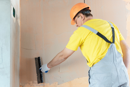 The worker is applying putty on a mesh on the wall. He is using a wide spatula. Фото со стока