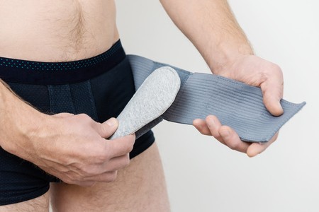 Bandage inguinal hernia. A man is putting the pad in a place hernia for better pressing. Stock Photo