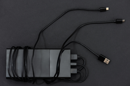 The power bank with charging cables on a dark background. Фото со стока