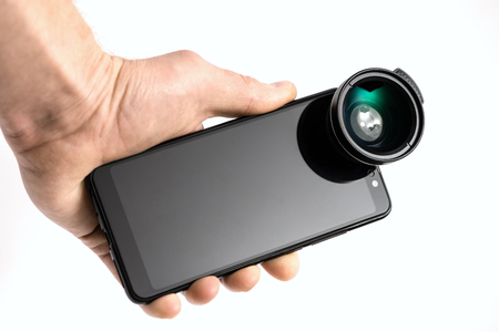 The human hand is holding a smartphone with an attached external lens.