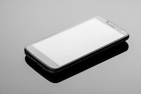 Modern smartphone on a dark glossy surface with reflection.