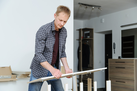 The man assembles the furniture at home. He sets the sidewall of the chest of drawers.
