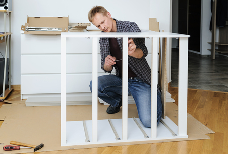 The man is assembling the furniture at home. He is mounting and fastening the frame of the chest of drawers. Фото со стока